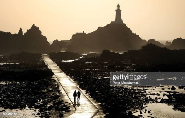 A couple walk on the causeway leading to the Corbiere lighthouse on March 1 2008 in Jersey Channel Islands Britain's most southerly island Jersey is...