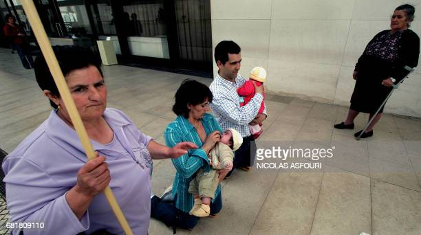 A couple walk on their knees as they pray for Pope John Paul II and hold their babies at the Fatima Sanctuary in Fatima 140 km north of Lisbon 01...
