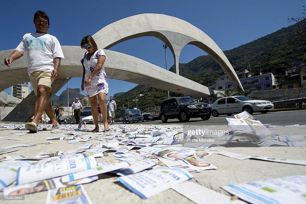 A couple walk over pamphlets as their head to a polling station in Rio de Janeiro's Rocinha shantytown on October 07, 2012 in Rio de Janeiro, Brazil.