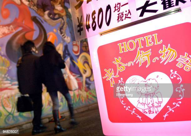A couple walk past a love hotel in Tokyo's Shibuya district Monday February 28 2005