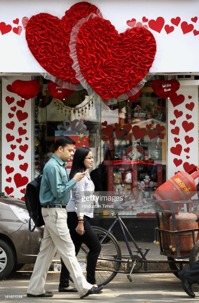Couple walk past a shop decorated for a Valentines day at Dadar on February 13, 2013 in Mumbai, India.
