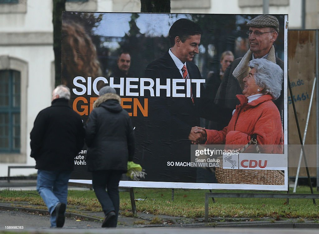 A couple walk past an election campaign billboard featuring Lower Saxony Governor and incumbent candidate of the German Christian Democrats (CDU) David McAllister on January 5, 2013 in Hanover, Germany. Lower Saxony is holding state elections on January 20 and many analysts see the election as a bellwether for national elections scheduled to take place later this year.