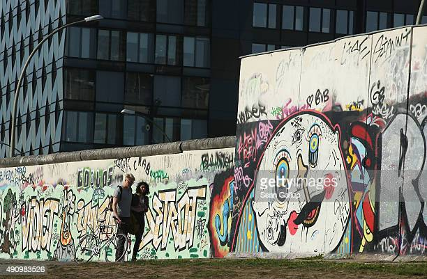 A couple walk past original sections of the former Berlin Wall at the East Side Gallery on the day before the 25th anniversary of German...