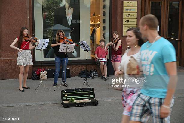 A couple walk past street musicians on May 19 2014 in Riga Latvia Founded in 1201 the city is a former member of the Hanseatic League and its...