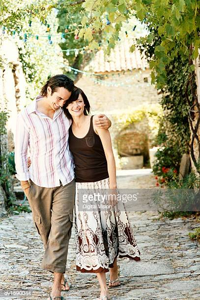 Couple Walk Side by Side on a Cobbled Path, Provence, France