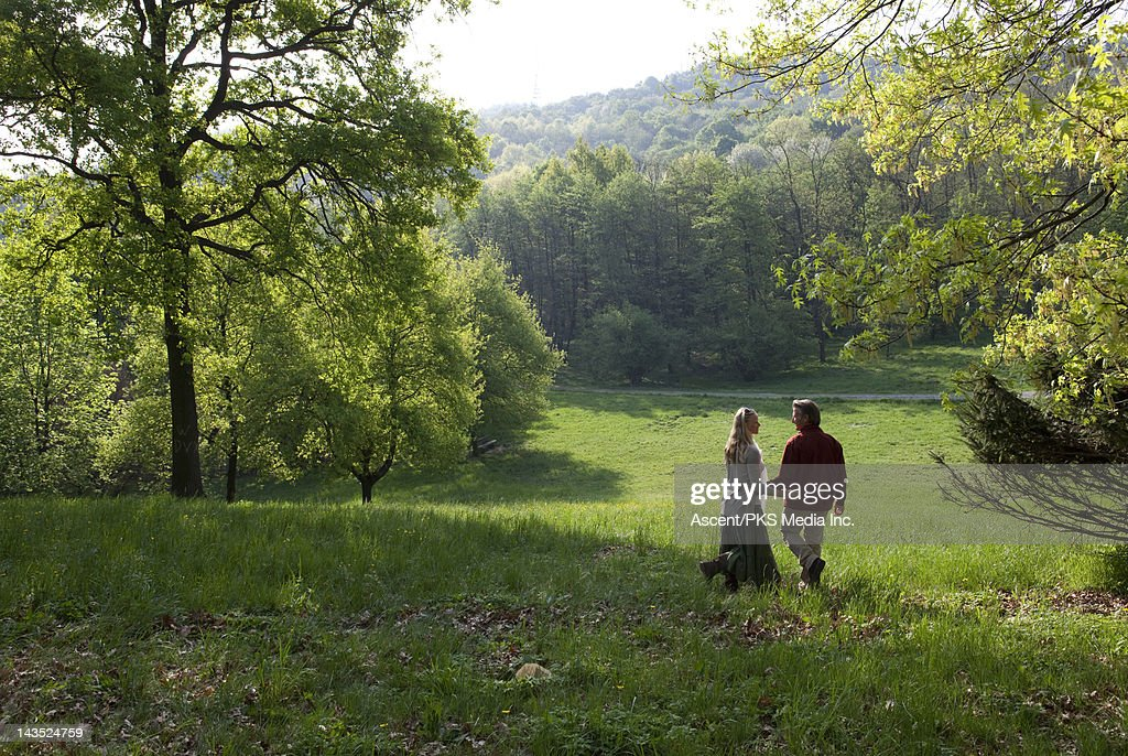 Couple walk through green parklands in spring : Stock Photo