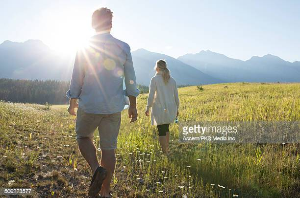 Couple walk through mountain meadow, sunrise