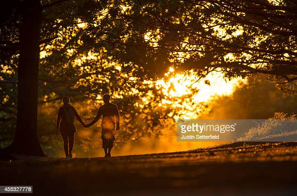 A couple walk through Richmond Park at sunset on September 12 2014 in London England Much of the UK continues to enjoy mild Autumn weather with...