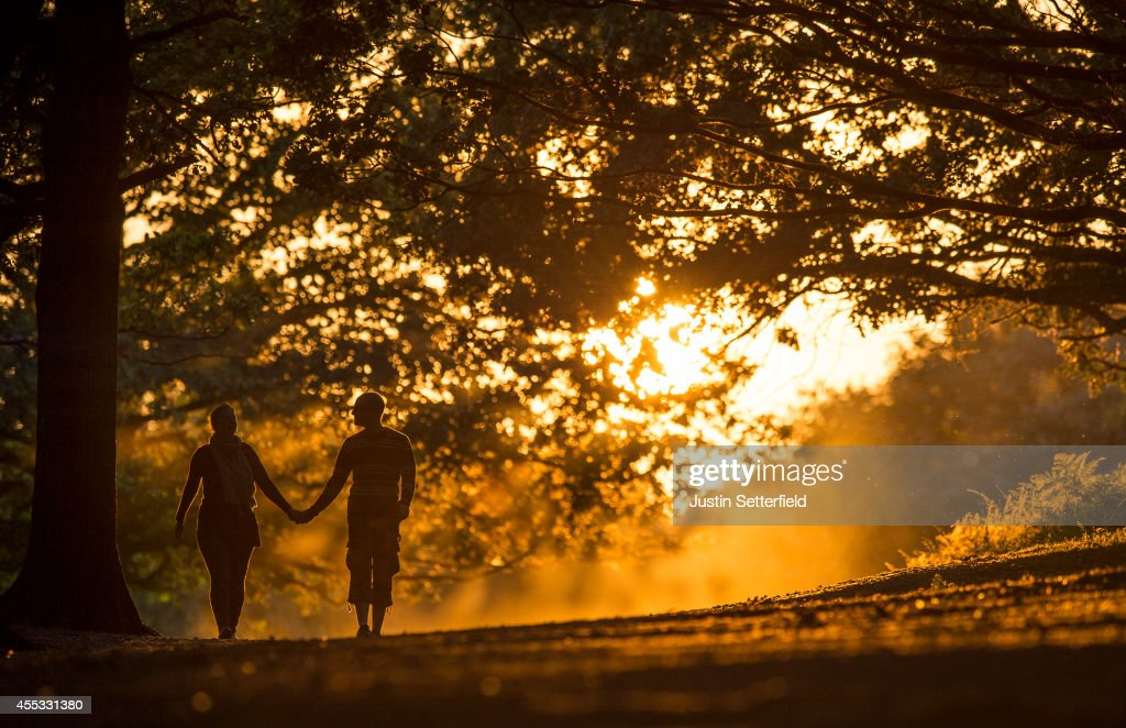 A couple walk through Richmond Park at sunset on September 12, 2014 in London, England. Much of the UK continues to enjoy mild Autumn weather with sunshine set to last for the next few days.