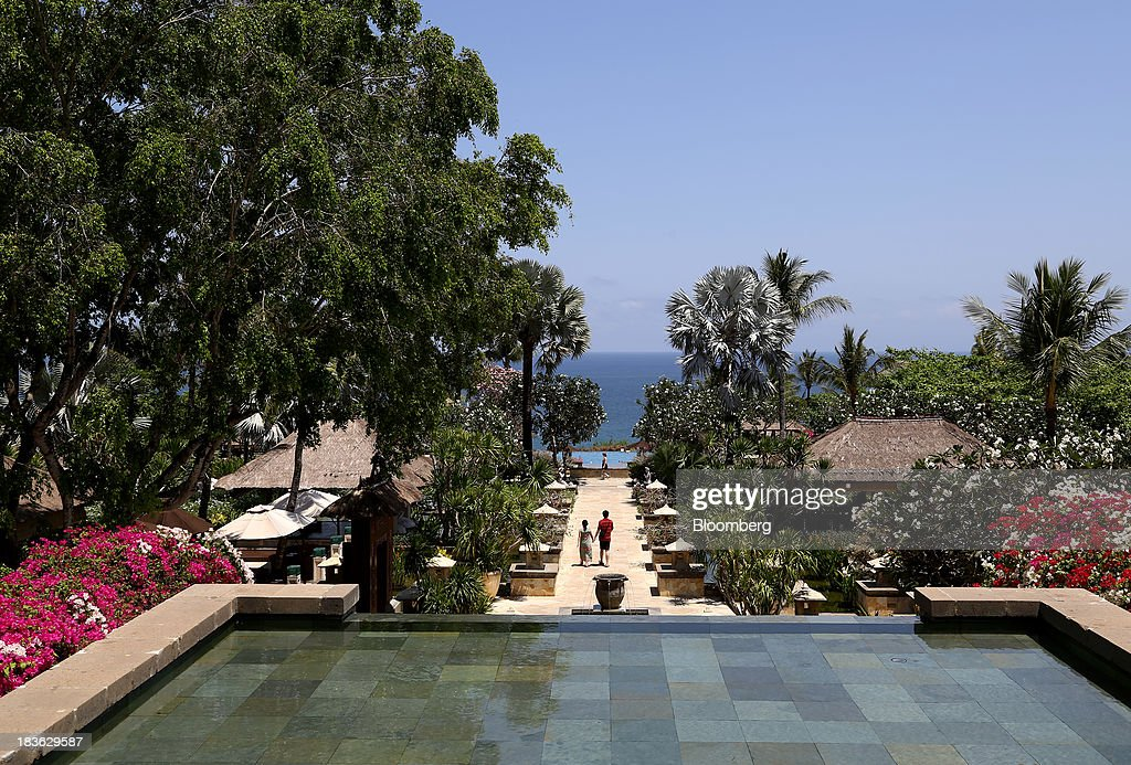 A couple walk through the grounds of the Ayana Resort and Spa hotel in Jimbaran, Bali, Indonesia, on Saturday, Oct. 5, 2013. Indonesia's central bank kept its key interest rate unchanged after its most aggressive tightening cycle in almost eight years as inflation pressure eased. Photographer: SeongJoon Cho/Bloomberg via Getty Images