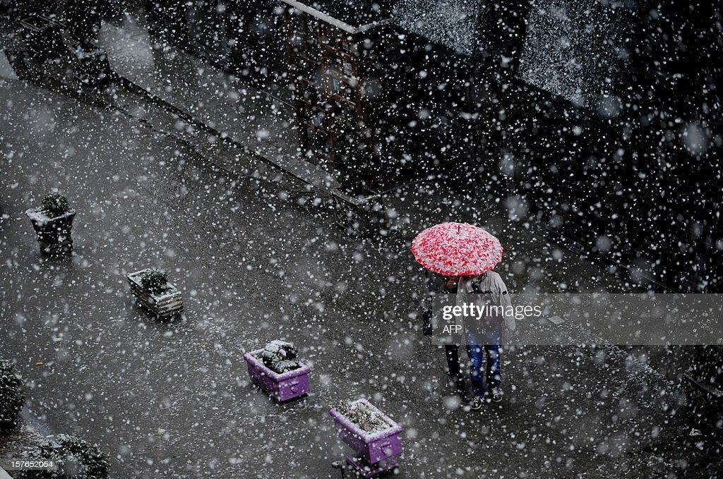 A couple walk under an umbrella during a heavy snowfall in Pristina on December 5, 2012.