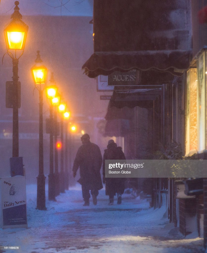 A couple walked along Harris Street as a winter storm, expected to dump as much as 24 inches of snow in the region, intensified in Newburyport.