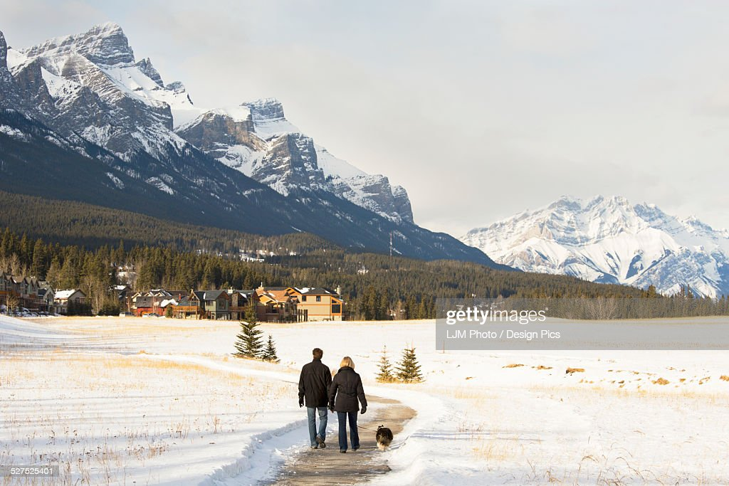 Couple walking a dog on a path in winter with the mountains ahead