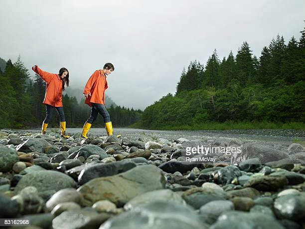 Couple walking across rocks of river bank.