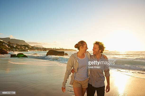 Couple walking along beach at sunset