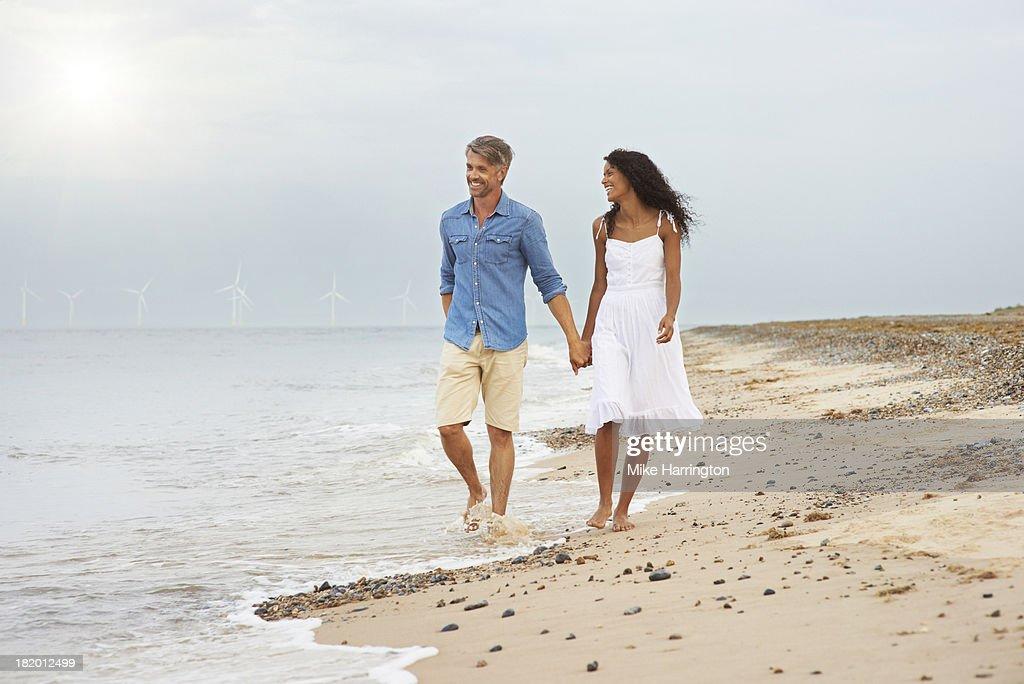 Couple walking along beach holding hands. : Stock Photo