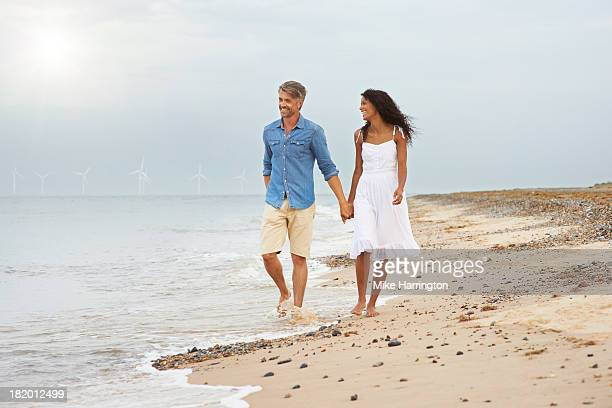 Couple walking along beach holding hands.