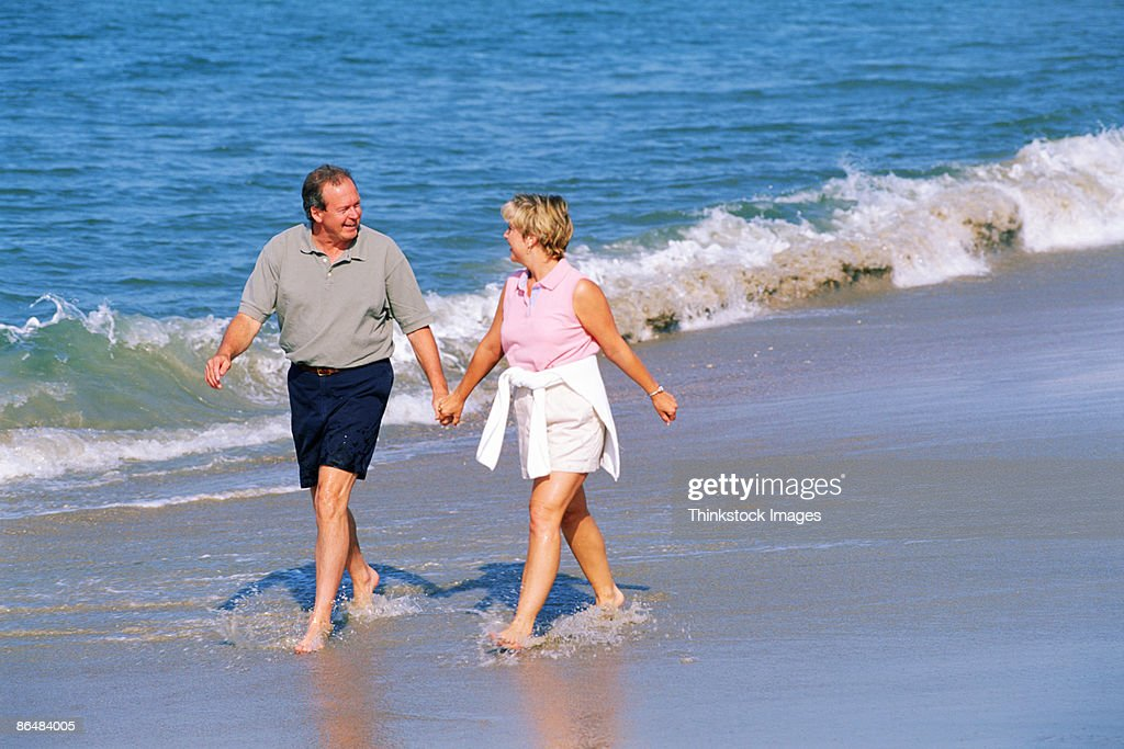 Couple walking along beach : Stock Photo