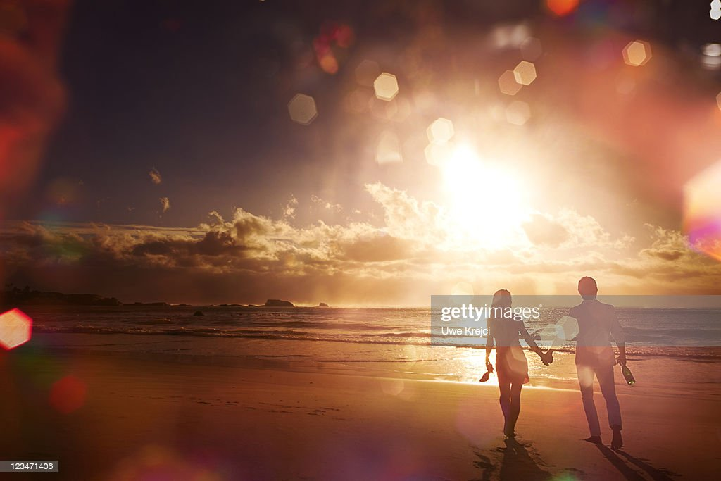 Couple walking along beach, silhouetted at sunset : Stock Photo