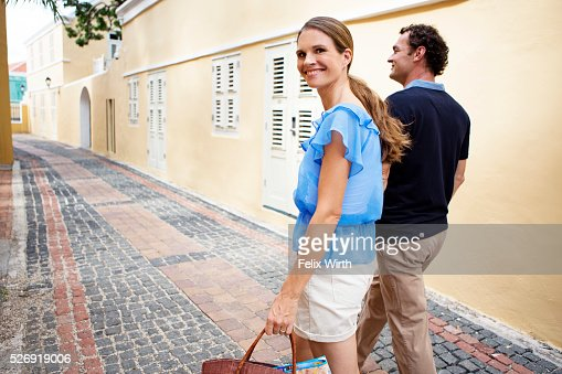 Couple walking along cobblestone street : Stock Photo