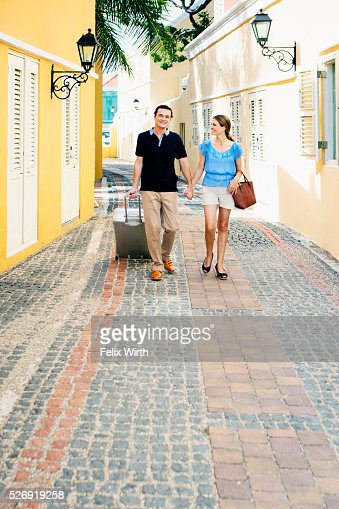 Couple walking along cobblestone street : Photo