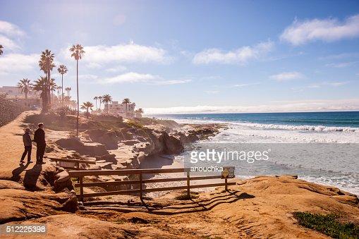 歩いている夫婦アロングラホーヤビーチ(カリフォルニア州、アメリカ)