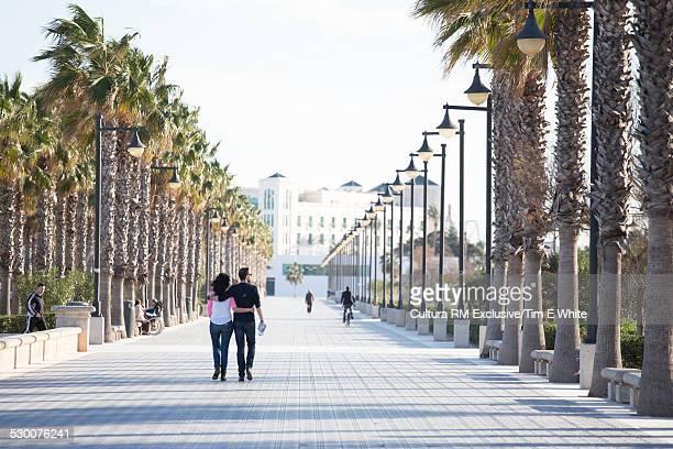 Couple walking along promenade, Valencia, Spain