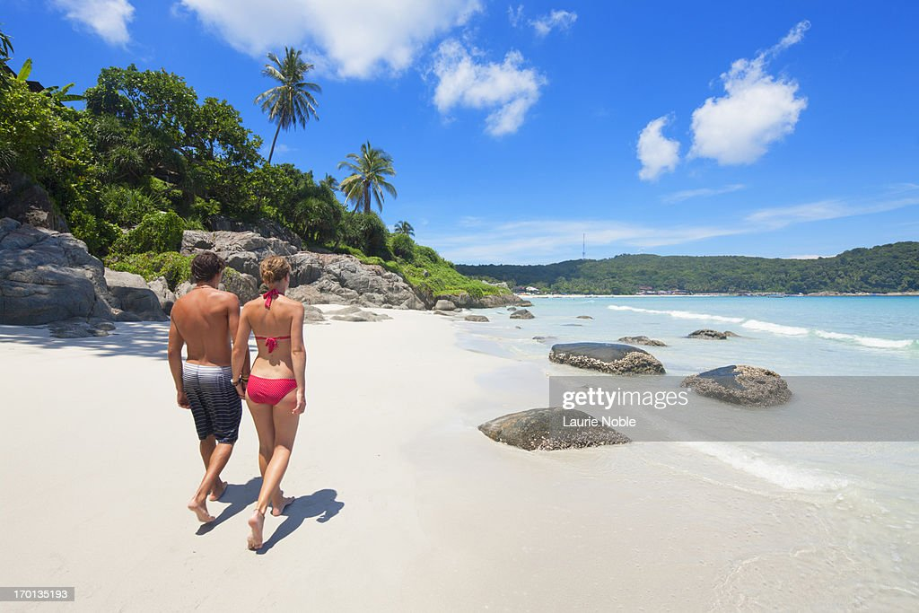 Couple walking along secluded beach : Stock Photo