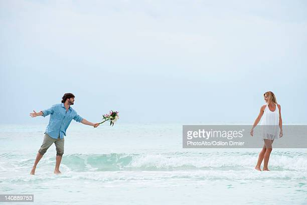 Couple walking apart in sea, man holding out bouquet