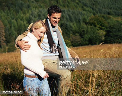 Couple Walking Arm And Arm Through Long Grass Smiling ...