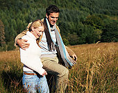 Couple walking arm and arm through long grass, smiling