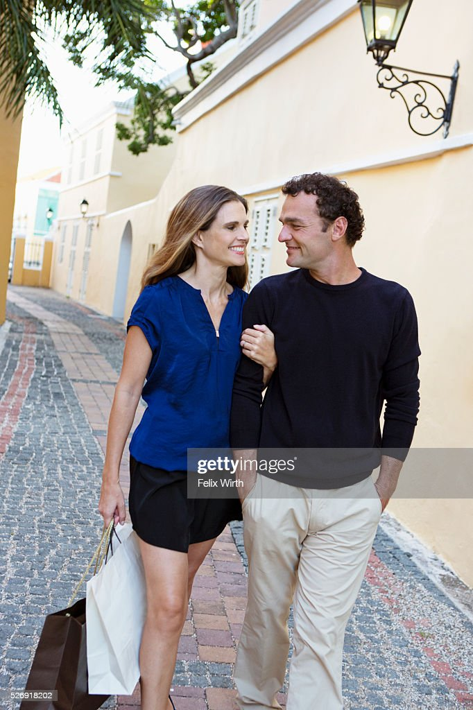 Couple walking arm in arm along cobblestone street : Stock Photo