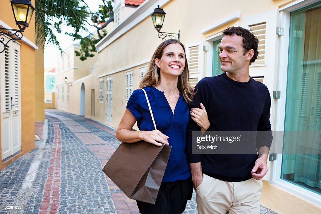Couple walking arm in arm along cobblestone street : Stockfoto