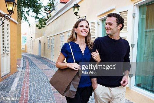 Couple walking arm in arm along cobblestone street : Stock-Foto