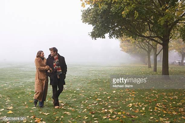 Couple walking arm in arm in misty park, autumn
