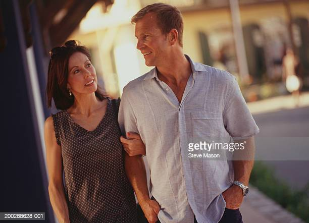 Couple walking arm in arm in quiet street
