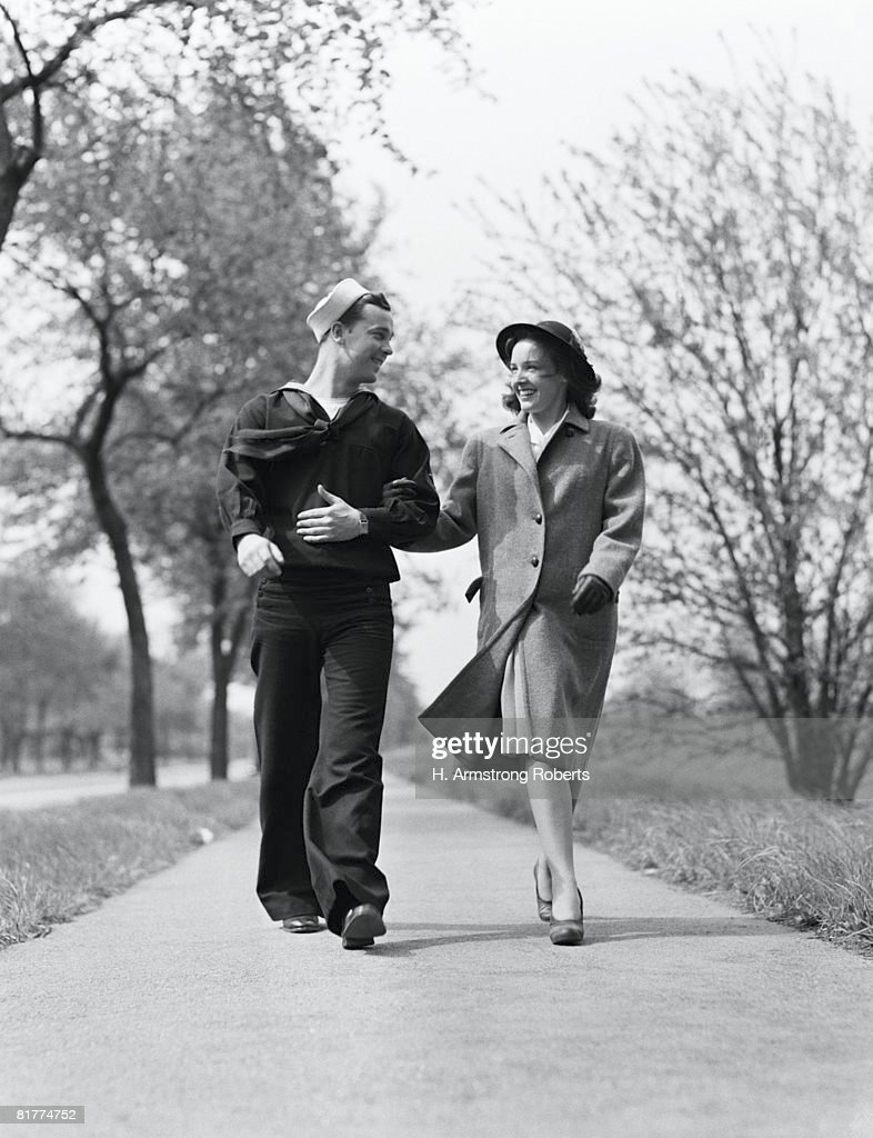 Couple walking arm in arm outdoors, man wearing naval sailor uniform, woman wearing coat, hat and gloves. : Stock Photo