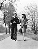 Couple walking arm in arm outdoors, man wearing naval sailor uniform, woman wearing coat, hat and gloves.