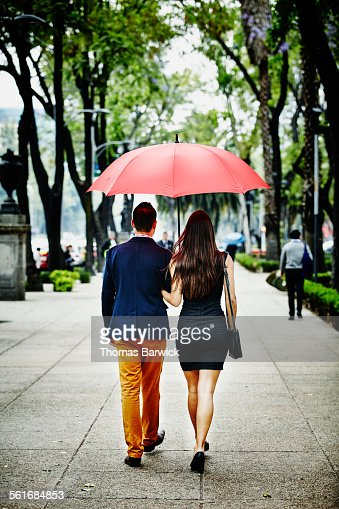 Couple walking arm in arm under umbrella
