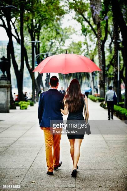 Couple walking arm in arm under umbrella