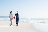 Senior couple holding hands at the beach on a bright sunny day. Mature couple in love holding hands and looking each other at the seaside. Smiling wife and happy husband walking barefoot on the white