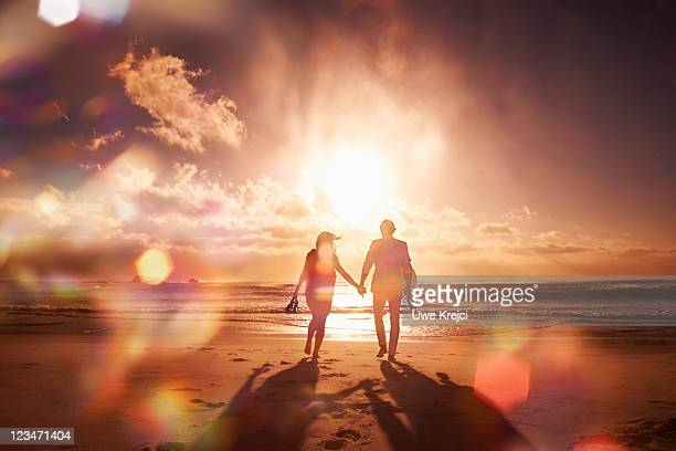 Couple walking at beach, silhouetted at sunset