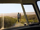 Couple walking away from camper van towards beach, view through camper van window