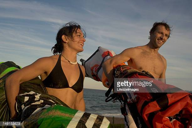 Couple walking away from sea, carrying kiteboard sails, laughing