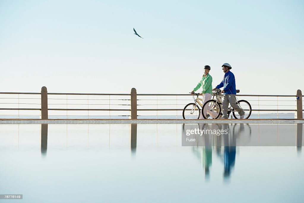 Couple Walking Bikes by the Water