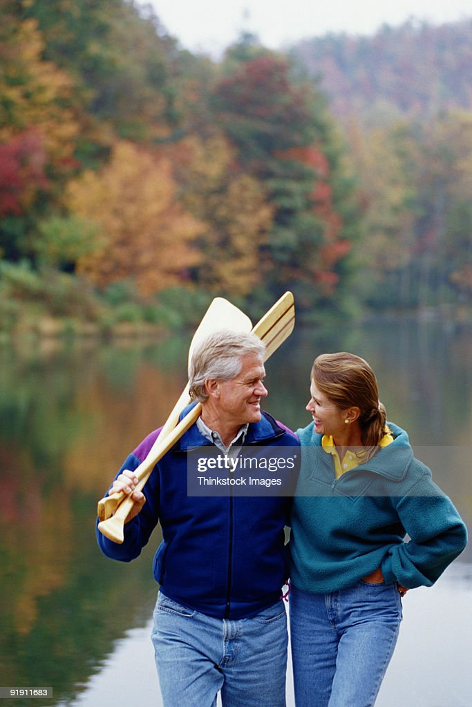 Couple Walking By Lake Man Holding Canoe Paddles Over His ...