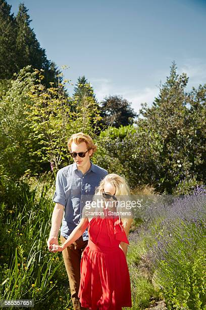 Couple walking by lavender in garden, Seattle, Washington, USA