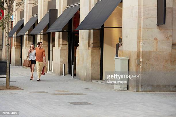 Couple walking by store on sidewalk