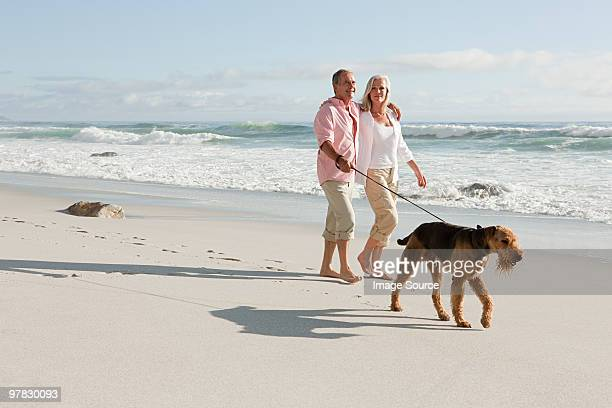 Couple walking dog by the sea