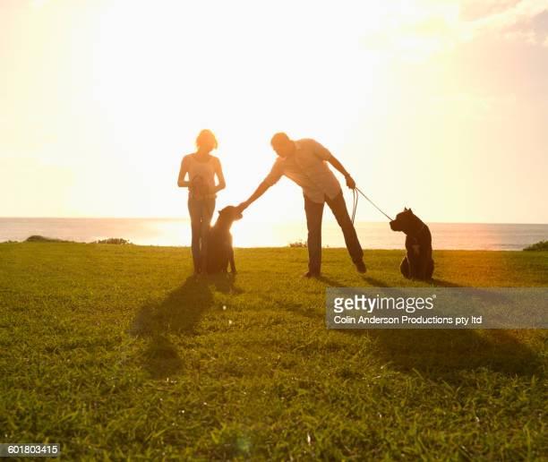 Couple walking dogs in field